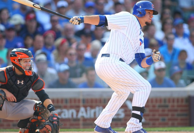 Aug 7, 2015; Chicago, IL, USA; Chicago Cubs catcher Kyle Schwarber (12) hits a two run RBI single during the fifth inning against the San Francisco Giants at Wrigley Field. Mandatory Credit: Caylor Arnold-USA TODAY Sports