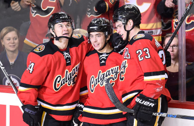 Dec 22, 2015; Calgary, Alberta, CAN; Calgary Flames left wing Johnny Gaudreau (13) celebrates his second goal of the night with center Jiri Hudler (24) and center Sean Monahan (23) against the Winnipeg Jets at Scotiabank Saddledome. Flames won 4-1. Mandatory Credit: Candice Ward-USA TODAY Sports